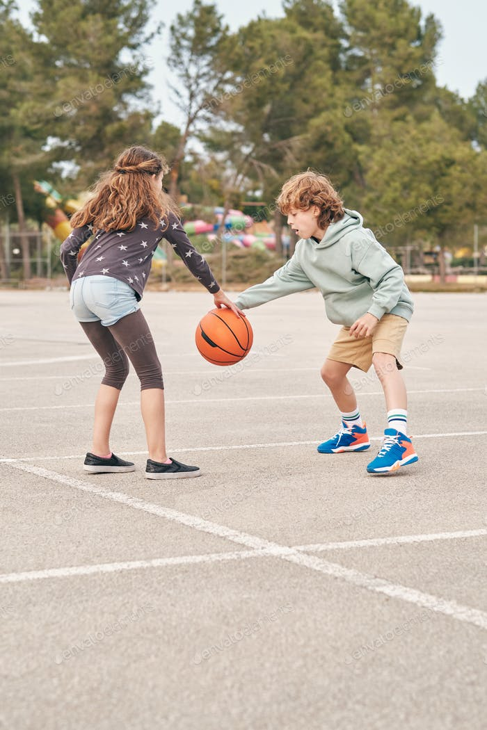 Teen friends playing basketball together