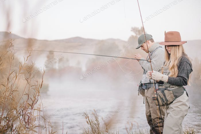 A couple fishing on a riverbank, tying the flys to the hooks for flyfishing.