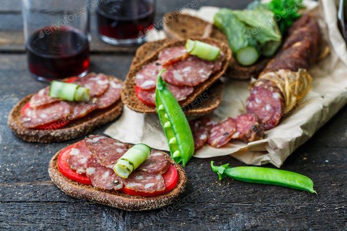 Roggen-Sandwich mit Wurst und Tomaten auf Holztisch.