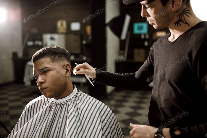 The barber scissors hair on the sides for a stylish black-haired man in the barbershop. Men's