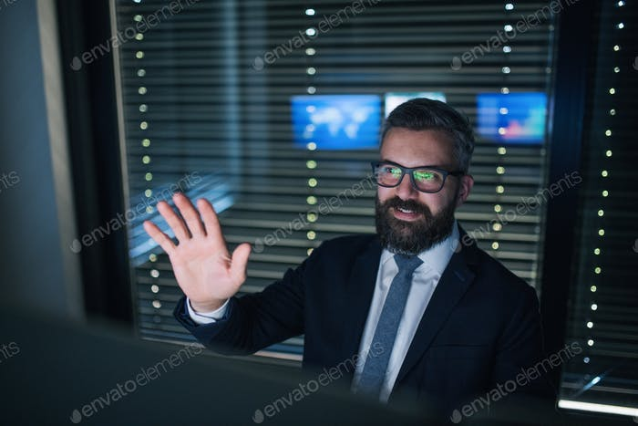 Front view of businessman having video call with colleague at desk