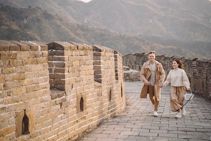 junges Paar läuft und wirbelnd an der Großen Mauer von China