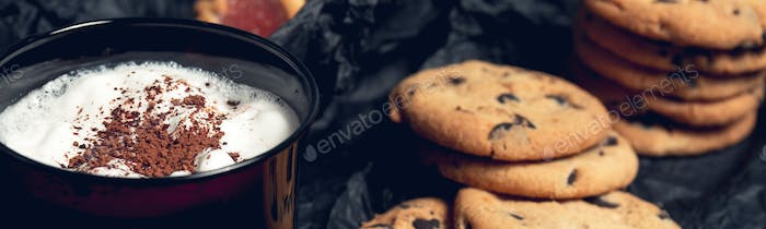 Banner of Cup of coffee, cappuccino with chocolate cookies and biscuits on black table background.