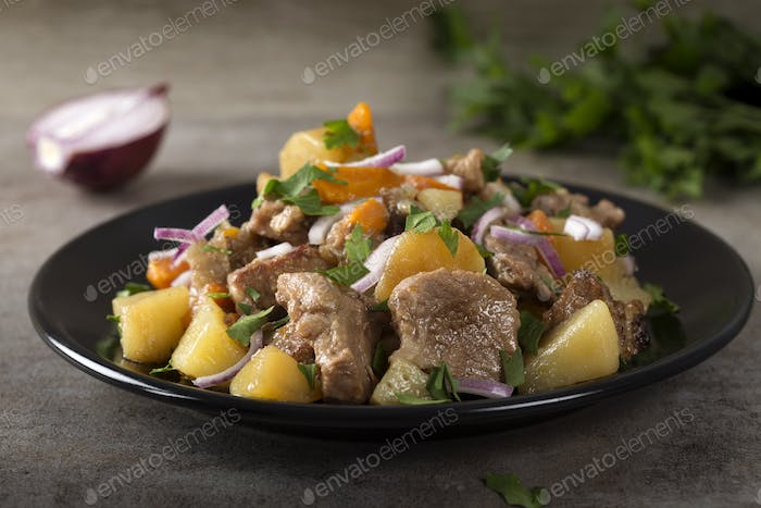 Baked potatoes, pork meat and carrots