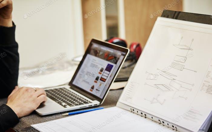 Möbeldesigner mit Skizzen und Laptop