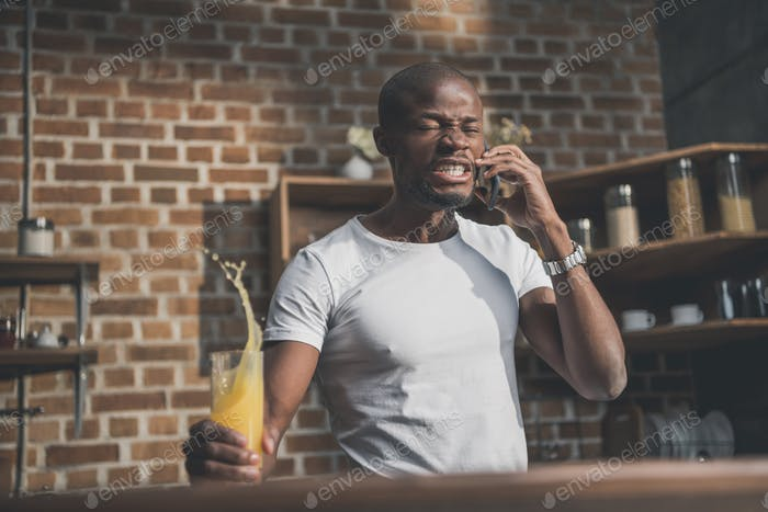 angry african american man shed juice during tense phone conversation