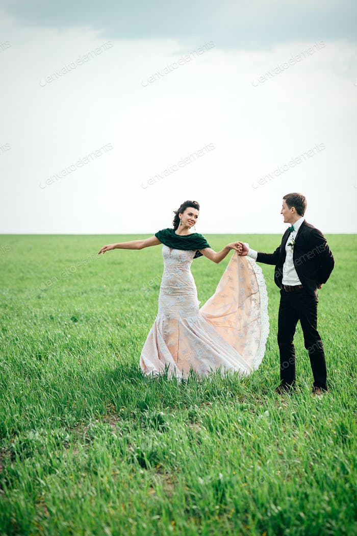 the groom in a brown suit and the bride in an ivory-colored dress on a green field