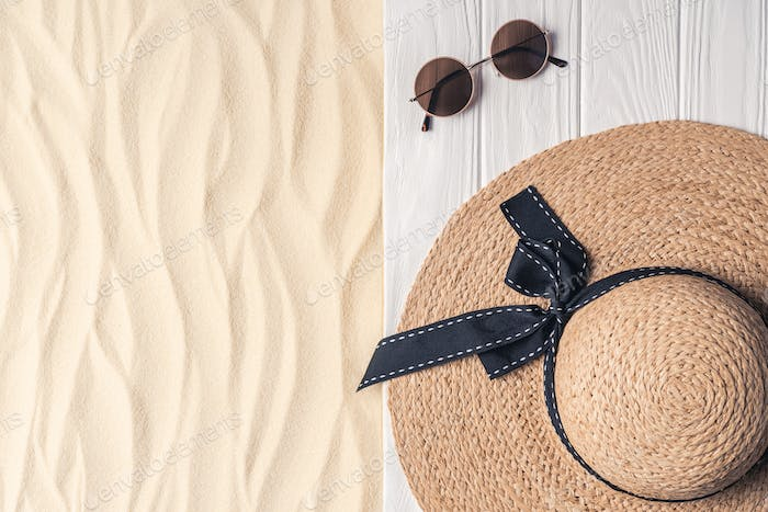 Straw hat and sunglasses on light sand