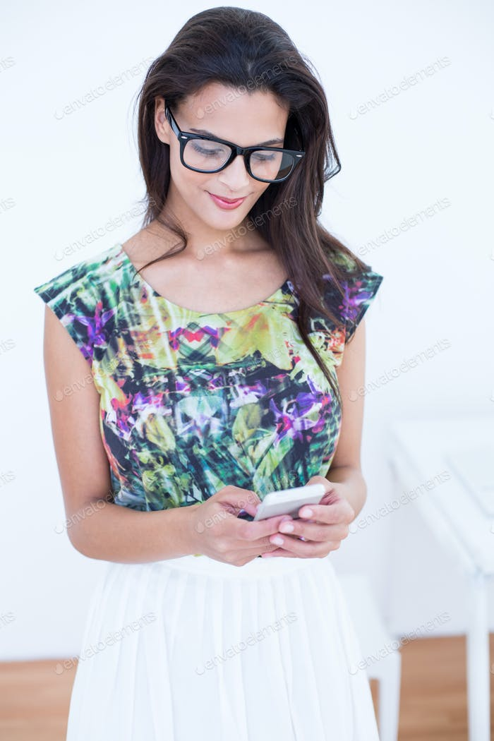 Smiling beautiful brunette standing in front of her computer and using her phone