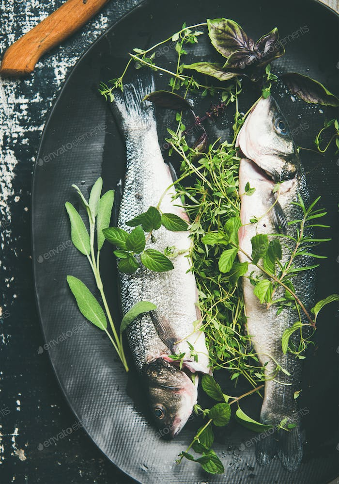 Flat-lay of raw uncooked sea bass fish with herbs
