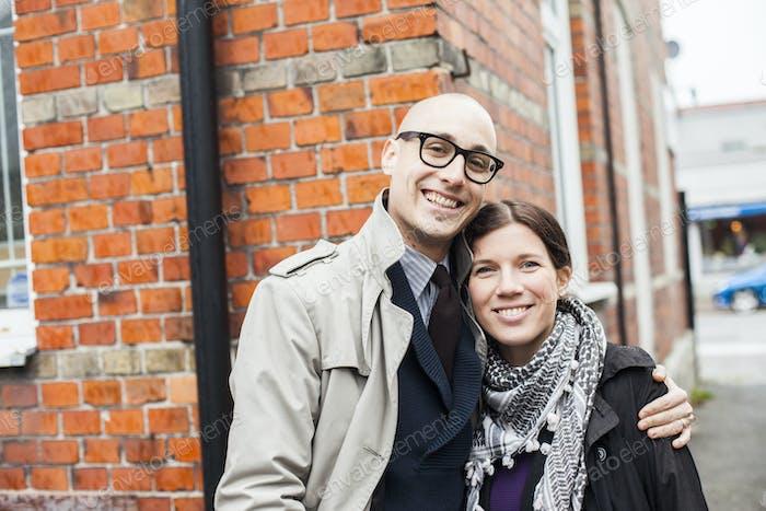 Portrait of happy couple standing against building