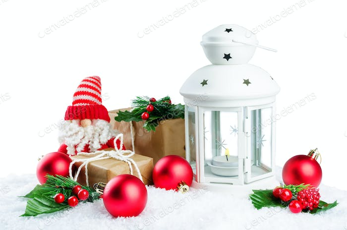 Christmas lantern with gifts, colored balls on a snow isolated b