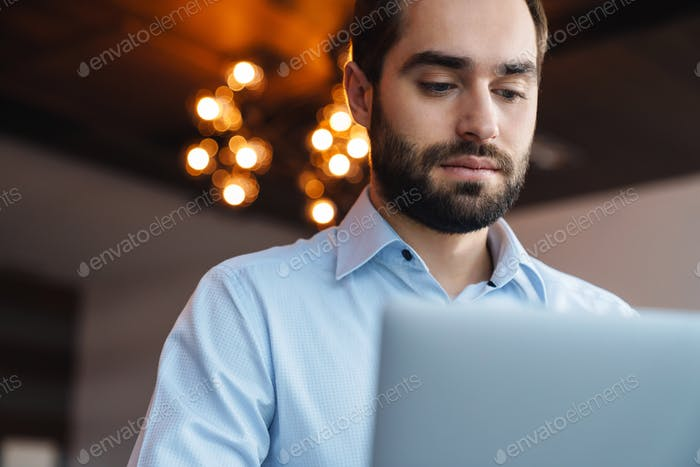 Portrait of handsome businessman using laptop while working in office