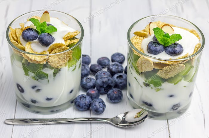Delicious yogurt dessert with blueberry, kiwi and cereals in the glass
