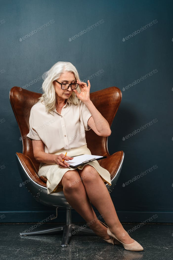 Serious mature old woman holding clipboard