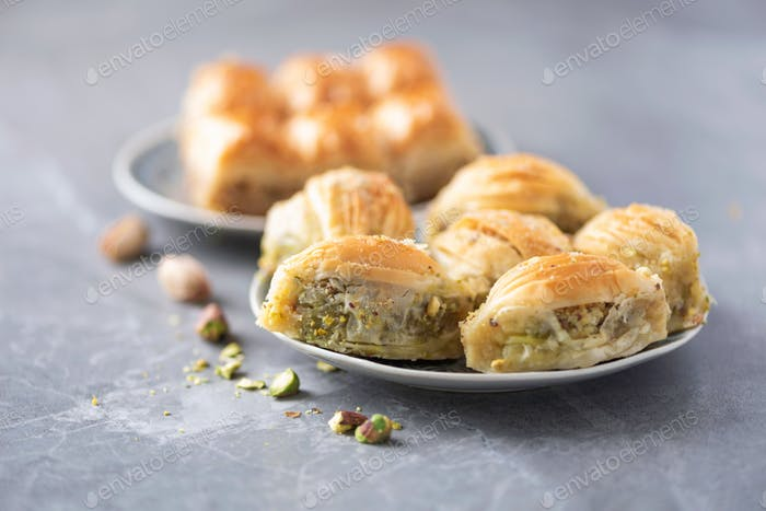 Middle eastern dessert baklava with pistachios on grey background
