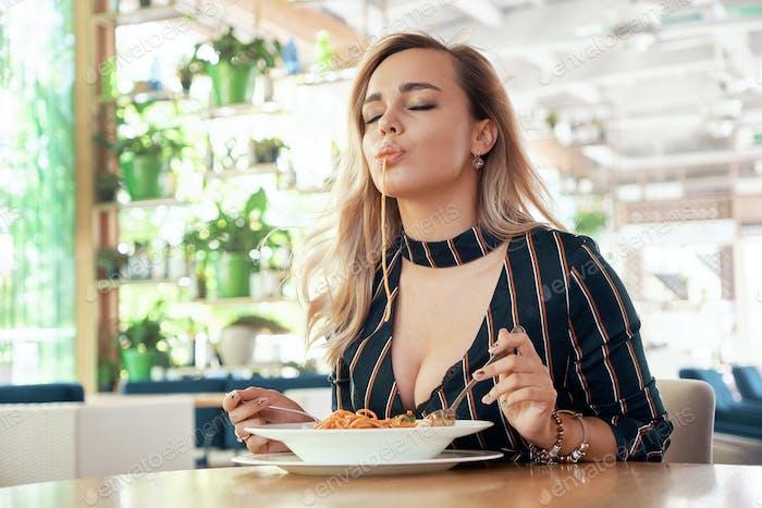Verführerische Frau isst Nudeln