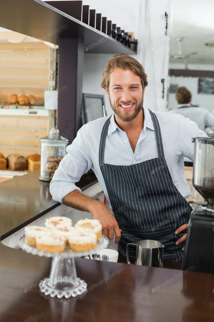 Handsome barista smiling at camera at the coffee shop