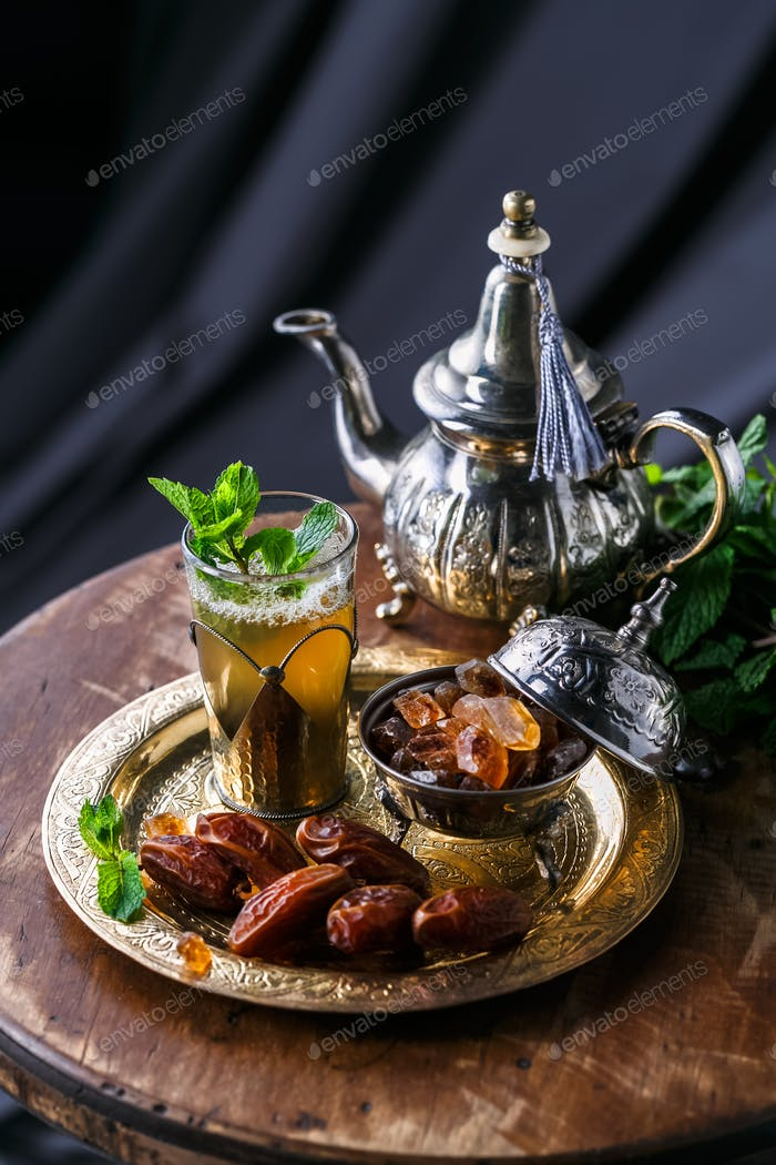 Moroccan tea with mint and sugar in a glass on a dark background