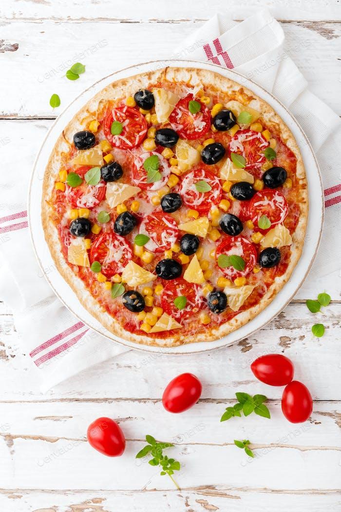 Pizza mit Tomaten, Mozzarella-Käse, Oliven, Mais und Basilikum