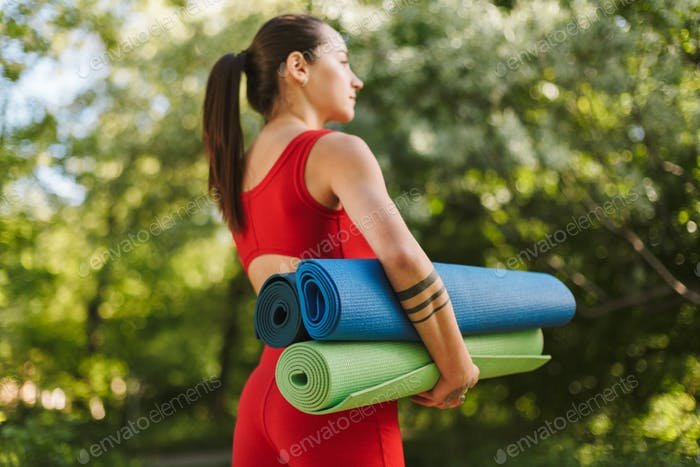 Young pretty woman in red jumpsuit standing from back with colorful yoga mats in hands in park