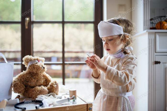 Small toddler girl with doctor uniform indoors at home, playing