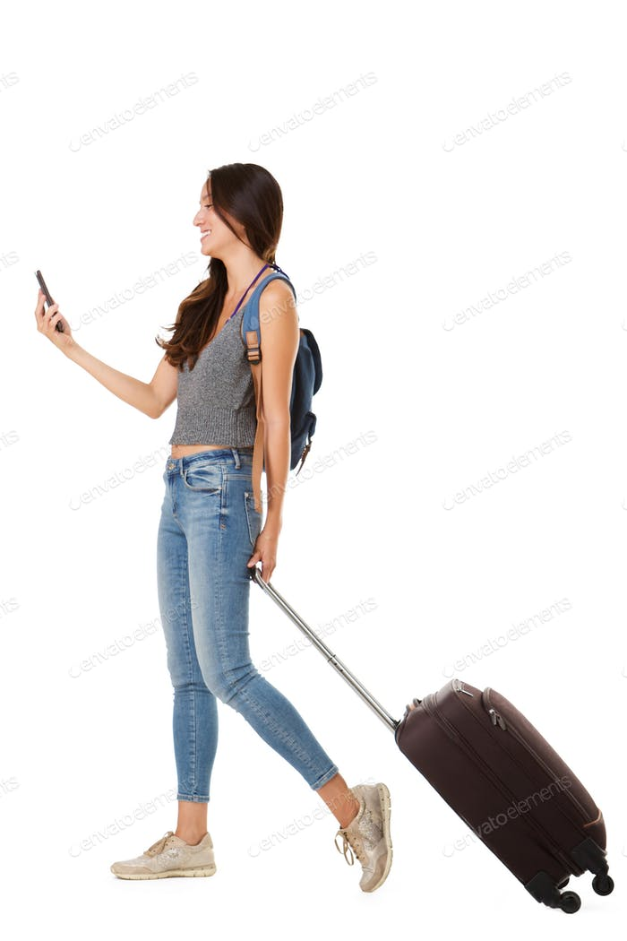 smiling asian woman walking against isolated white background with suitcase and cellphone