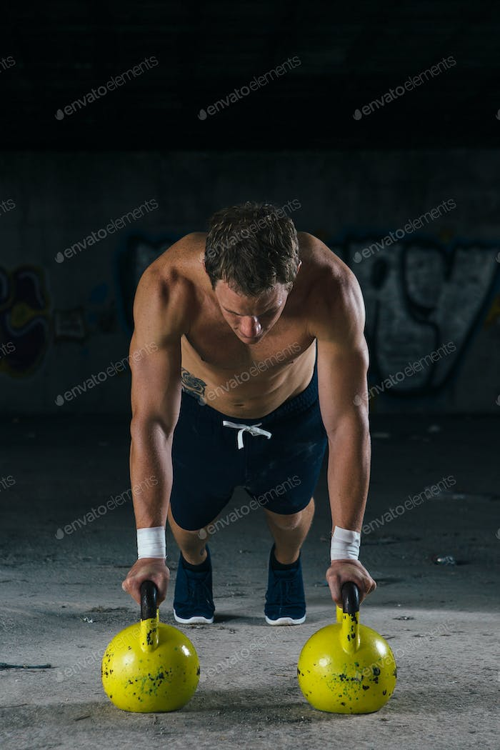 Muscle man doing push ups with dumbbels