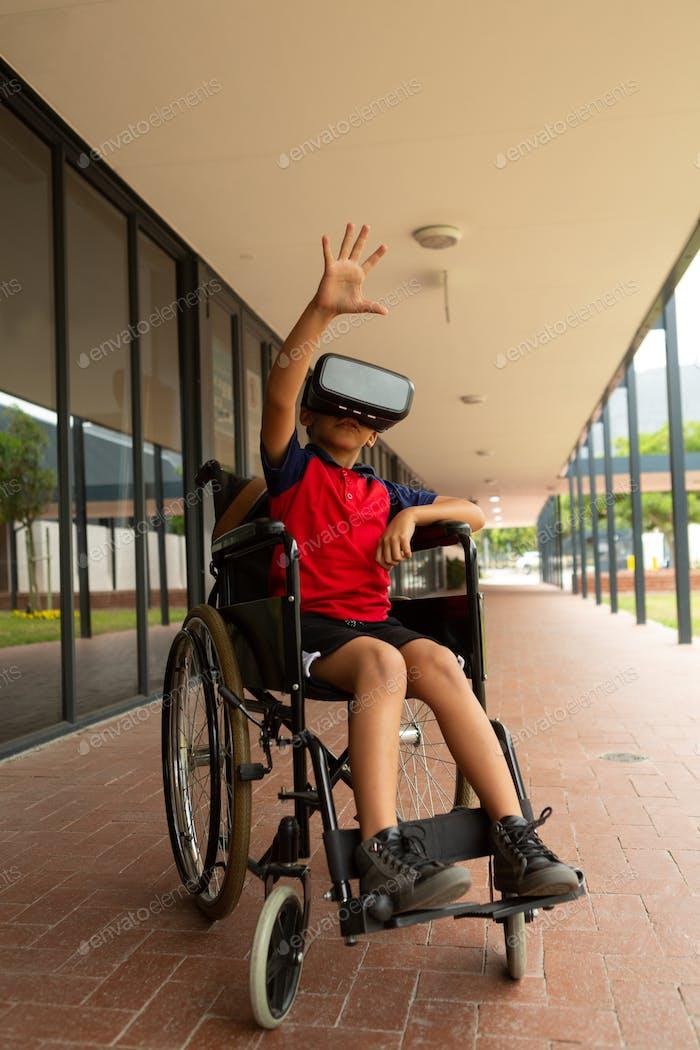 Mixed-Race behinderte Schuljunge mit Virtual Reality Headset mit einer Hand in der Luft im Flur