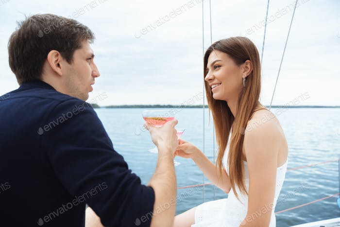 Happy couple drinking vodka cocktails at boat party outdoor, cheerful and happy