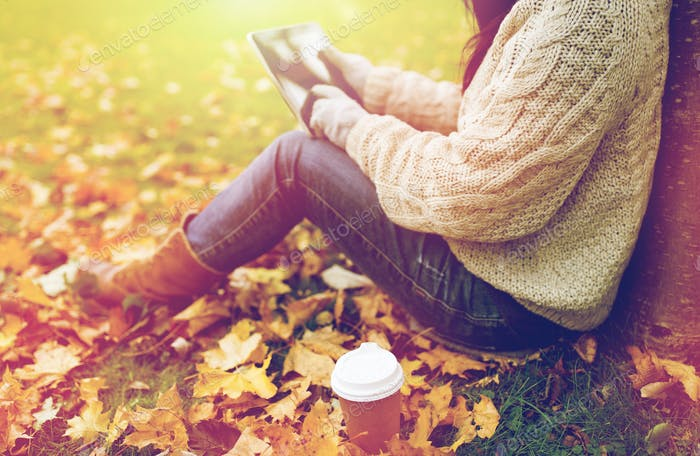 woman with tablet pc and coffee in autumn park