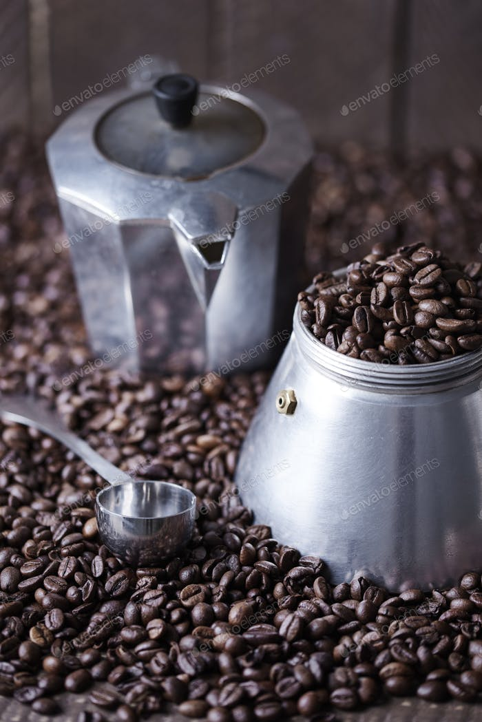 Old fashioned coffee mill and spoon among coffee bean