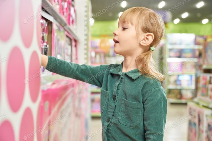 Little girl choosing toy in big shopping centre
