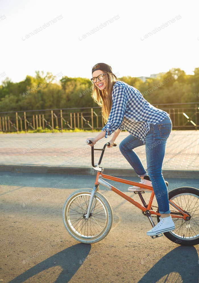 Lovely young woman in a hat riding a bicycle in the sunlight out