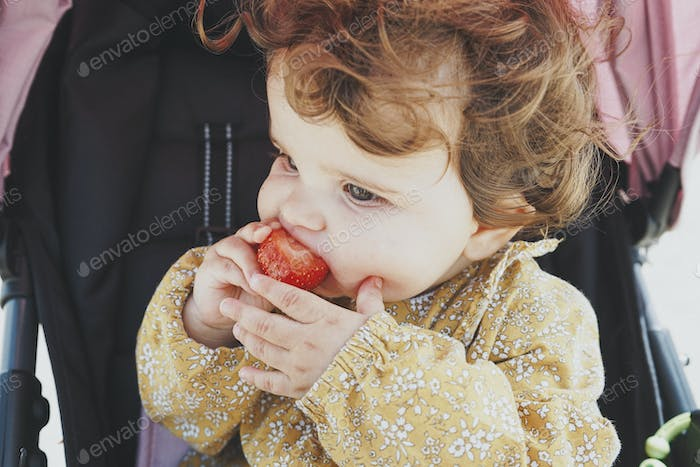 Little baby girl eating a strawberry