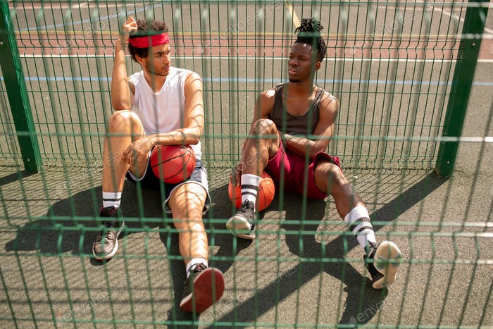 One of young intercultural basketballers telling his friend of game details