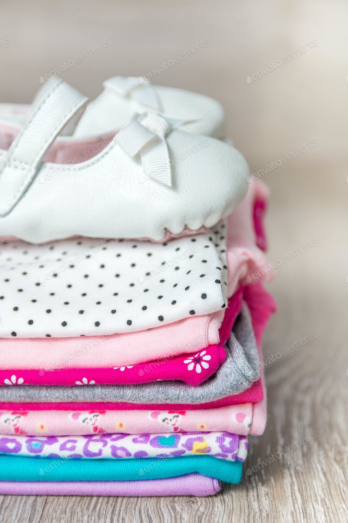 Folded pink and white bodysuit with shoes on it grey wooden background. diaper for newborn girl