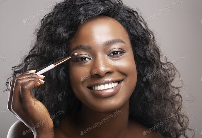 Closeup portrait of attractive black woman applying eyeshadows with brush