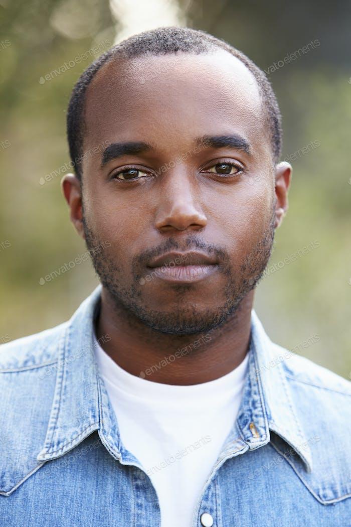 Young African American man in denim shirt, vertical portrait