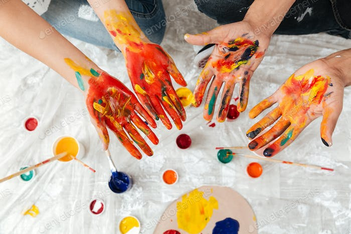 Hands of couple dirty in colorful paints over white background