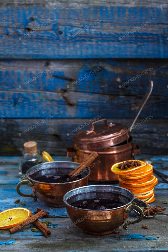 Mulled wine in copper cups with spices and citrus fruit, copy space