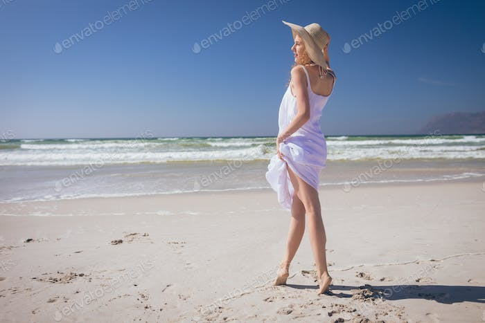Beautiful woman giving pose while standing at beach on a sunny day