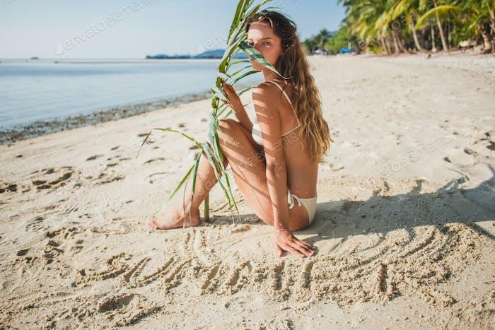 young skinny woman in white bikini swimwear holding leaf of palm tree