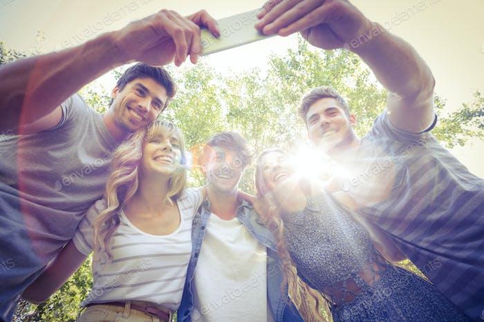 Glückliche Freunde im Park nehmen selfie an einem sonnigen Tag