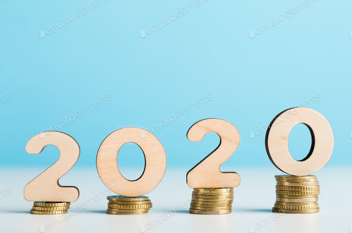 Big 2020 wooden numbers on coins showing financial growth