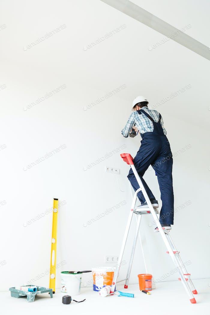 Vista posterior foto del Hombre constructor en plano hacer reparación.