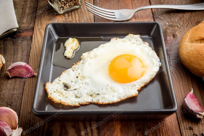 fried egg in black porcelain tray on rustic wood