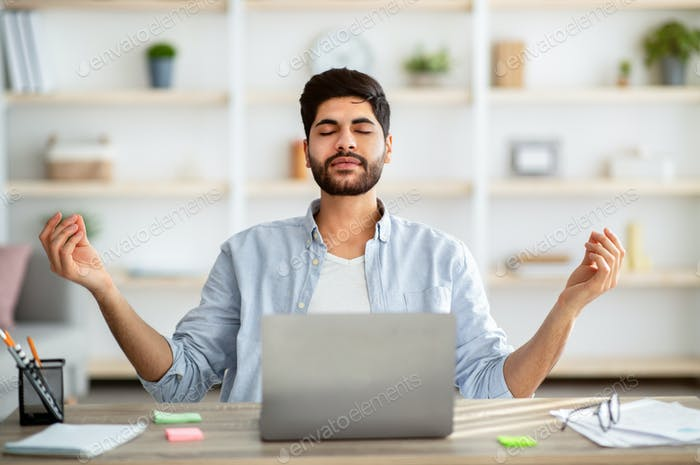 Keep calm. Arab freelancer meditating while working on laptop, sitting with eyes closed at his