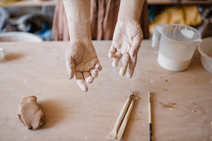Female master hands covered with clay, pottery