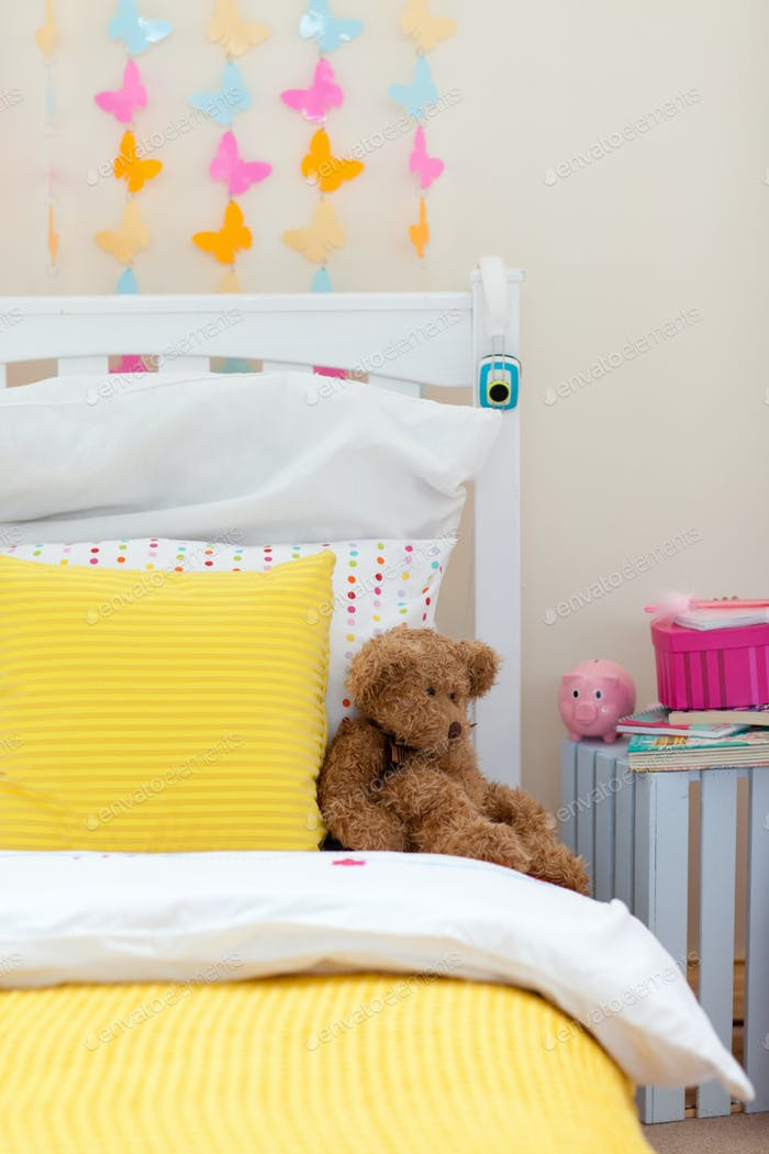 Child's bedroom with a teddy bear on the bed
